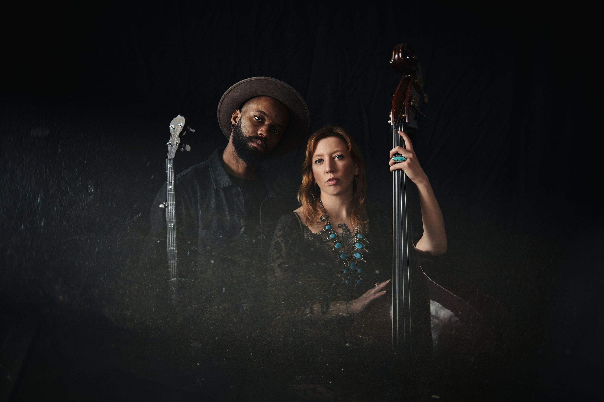 man with banjo and woman with bass. photo by Kat Schleicher