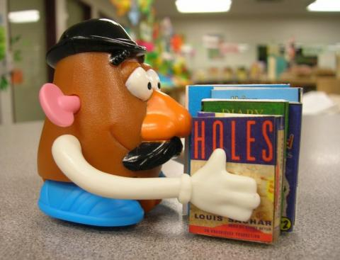 Mr. Potato Head holding books like Holes.